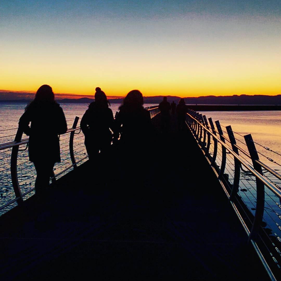 The blurred, dark silhouettes of about 6 people as the walk out on the Breakwater, which is a cement elevated walk way that protrudes out into the ocean and leads to a small, unmanned lighthouse. Past the curved fence on either side of the walk way that ocean is picking up the blue and peach colours of the sky as the sun begins to rise. The sky is a warm peach or orange on along the horizon, and fades to white and the blue or grey higher up.
