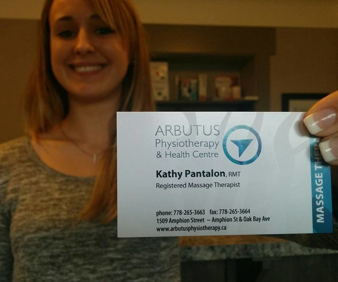 "A blonde woman to the left it standing in a light brown office and smiling. She is out of focus. She is holding a card out in front of her to the right, which is in focus. It has the Arbutus logo of a blue arrow in a blue circle at the top and says ""Kathy Pantalon, Recistered Massage Therapist, phone 778-265-3663, fax 778-265-3664. 1509 Amphion Street -- Amphion St. and Oak Bay Ave, www. arbutusphysiotherapy.ca."""