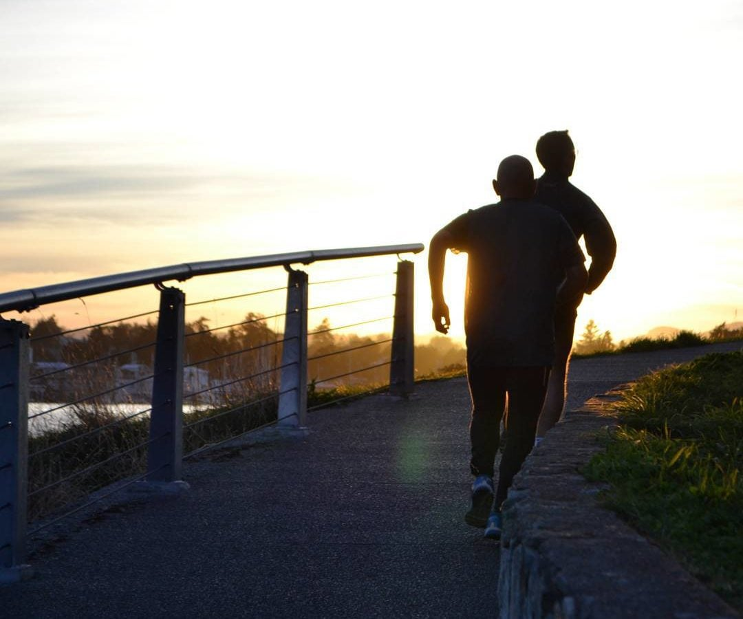 The silhouettes of two runners to the right are going up a slight hill away from the camera. The sun is setting or rising in front of them in the distance, and to their left and pst a metal railing is the ocean and the silhouette of trees on the other side of the water.