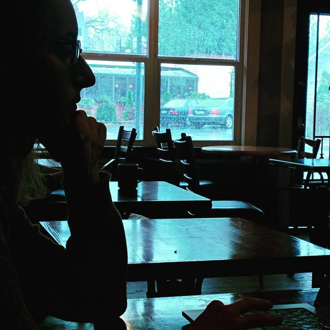 A silhouette of a person with glasses sitting in profile (sideways) for the camera. They are sitting at a table working on a laptop. There are other empty tables behind them. They are framed by a bright window divided into four square panes, and it is raining hard outside.
