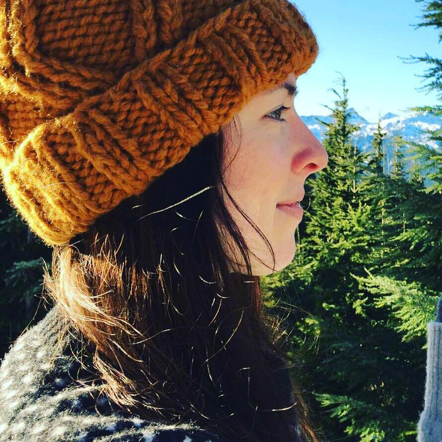 A woman in profile and facing the right is in the foreground. We see her from the shoulders up. Her nose is red suggesting she's a bit cold, and she has long brown hair under a mustard yellow tuque. There is a forest of evergreen trees behind her, and snowy mountains in the distance. The sky is clear, bright, and blue.