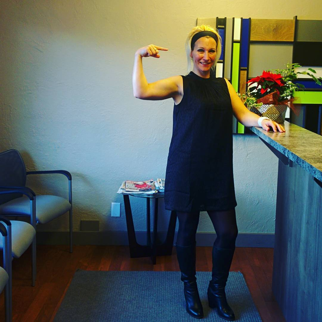 A woman in a black dress standing in an office with her left arm on a marble bar like front desk and her right arm flexed up with the index finger pointing in the direction of the front desk. She is smiling.