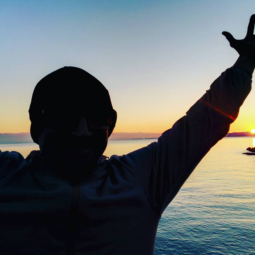 The silhouette of a man who appears to be wearing sunglasses and a tuque is slightly left of center. We cannot see his right arm, but his left are is reaching up and out above his head. We see him from the chest up. There is water behind him, as well as the setting sun. The horizon is orange, which fades to white and then dusky blue higher up. The water picks up these colours.