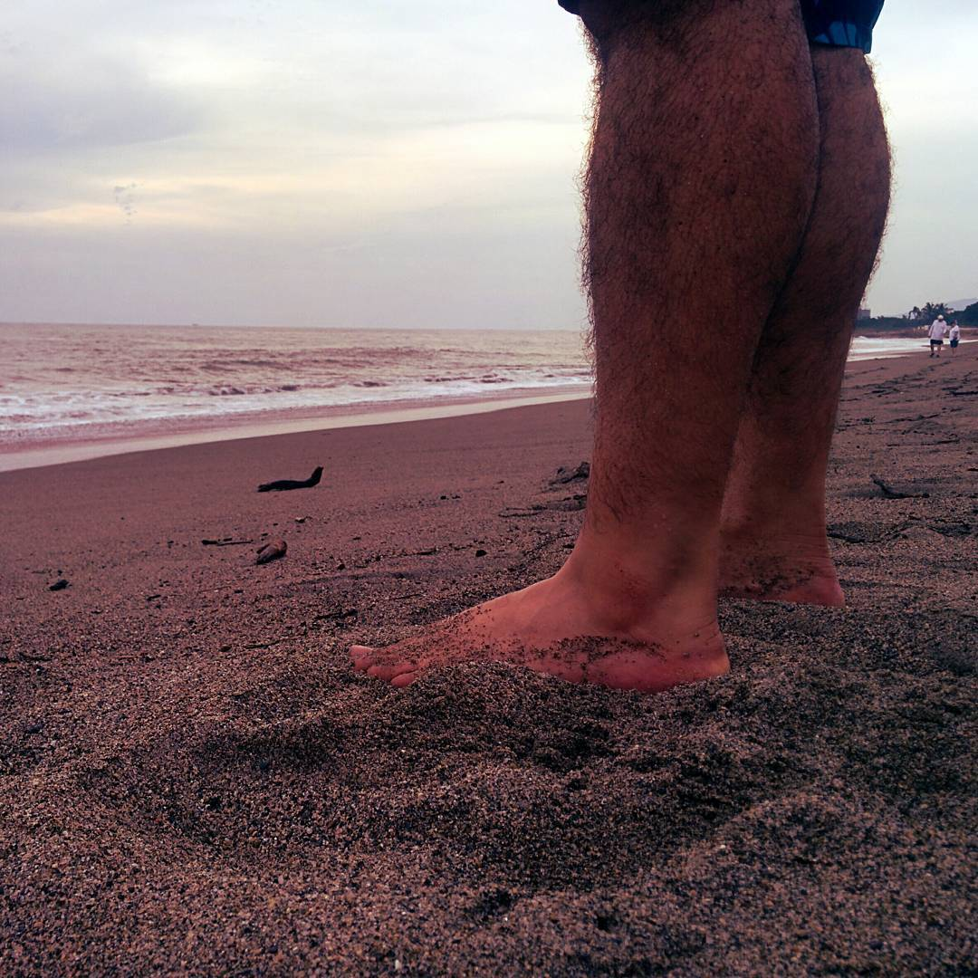 A man's legs and bare feet from the knee down standing on a sandy beach with his toes pointing towards the ocean. It is a bright, but slightly grey day. The ocean is to the left.