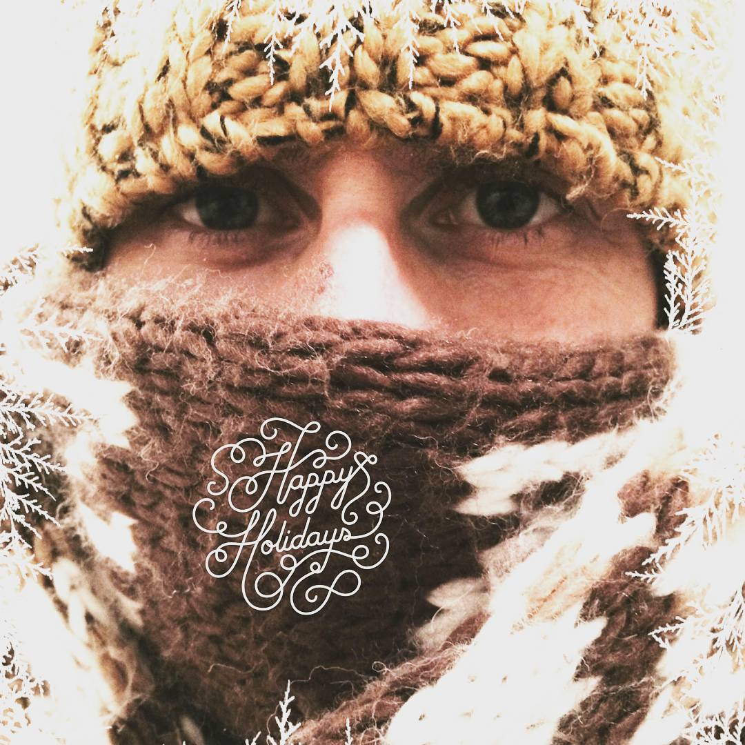 A close up of a woman's face. We can only see her eyes and the bridge of her nose because she is wearing a broad brown scarf and a brown tuque.