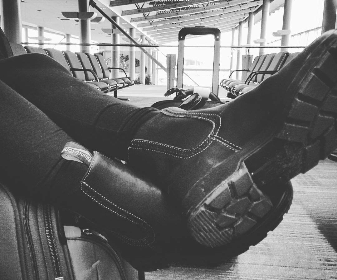 A black and white close up photo of a person's crossed legs from the shin down. Their legs are crossed on a suitcase inside a terminal with rows of seats in the background, and there are wearing blundstone boots.