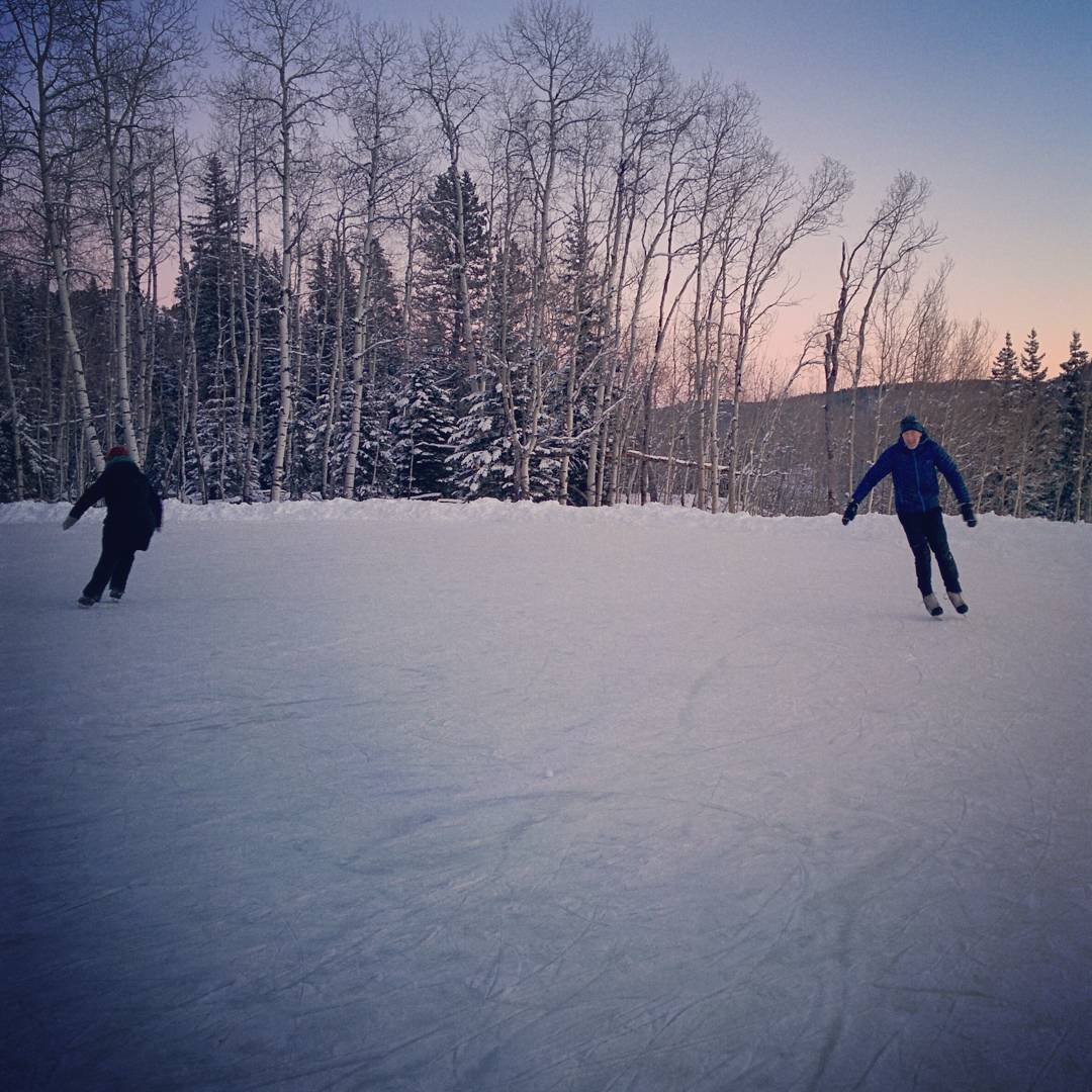 Two people, one in a black winter coat and the other in a blue one, are skating on an outdoor rink in black hockey skates. Behind them are trees -- some evergreen and some without leaves -- and then mountains in the distance. The sky is pink on the horizon fading to darker blue higher up.