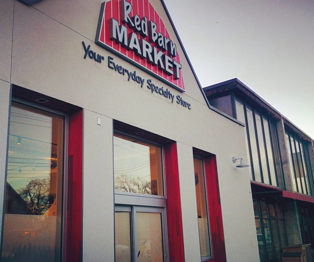 "A photo looking up at the front of a Red Bard Market. The camera is to the left of the facade. A red barn sign near the top says ""Red Barn Market"" and below that it says ""Your Everyday Specialty Store. The rest of the front is light brown with red trim on the inside of the door and the windows on either side. The sky in the background is grey."