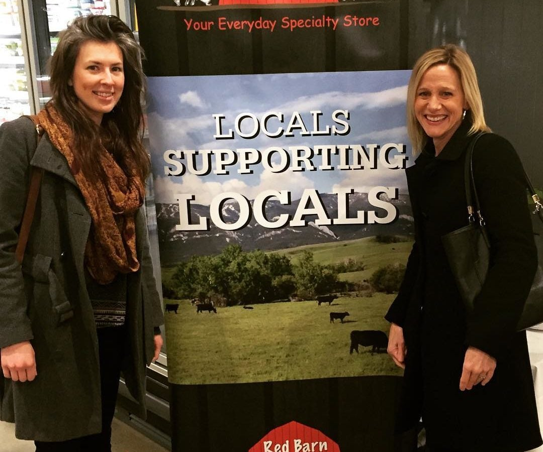 """Libby, a woman with dark hair and a green coat, and Sandy, a woman with blonde hair and a black coat, are standing indoors on either side of a sign that has a photo of a field with cows and over that it says """"Locals Supporting Locals."""" Both women are smiling."""