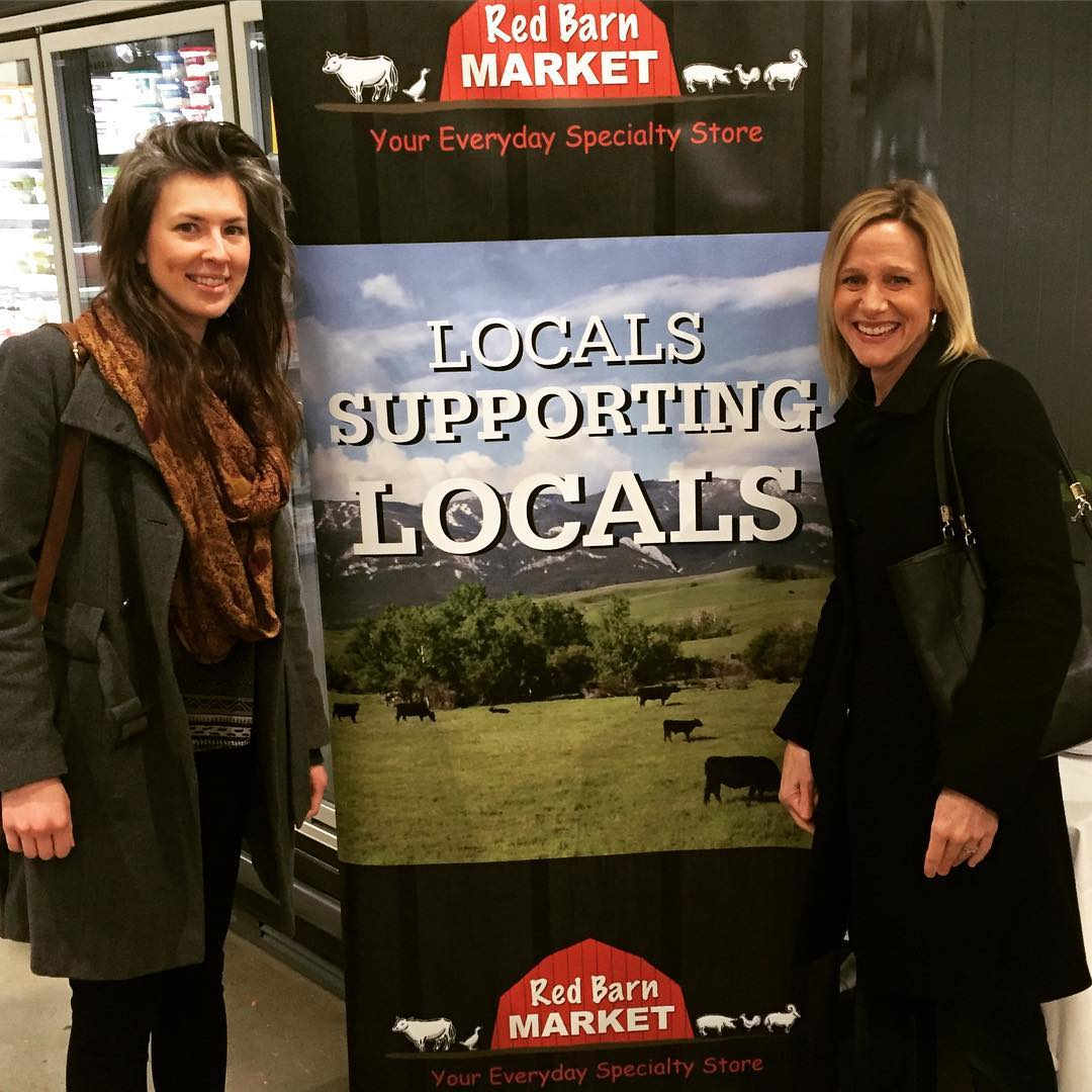 "Libby, a woman with dark hair and a green coat, and Sandy, a woman with blonde hair and a black coat, are standing indoors on either side of a sign that has a photo of a field with cows and over that it says ""Locals Supporting Locals."" Both women are smiling."