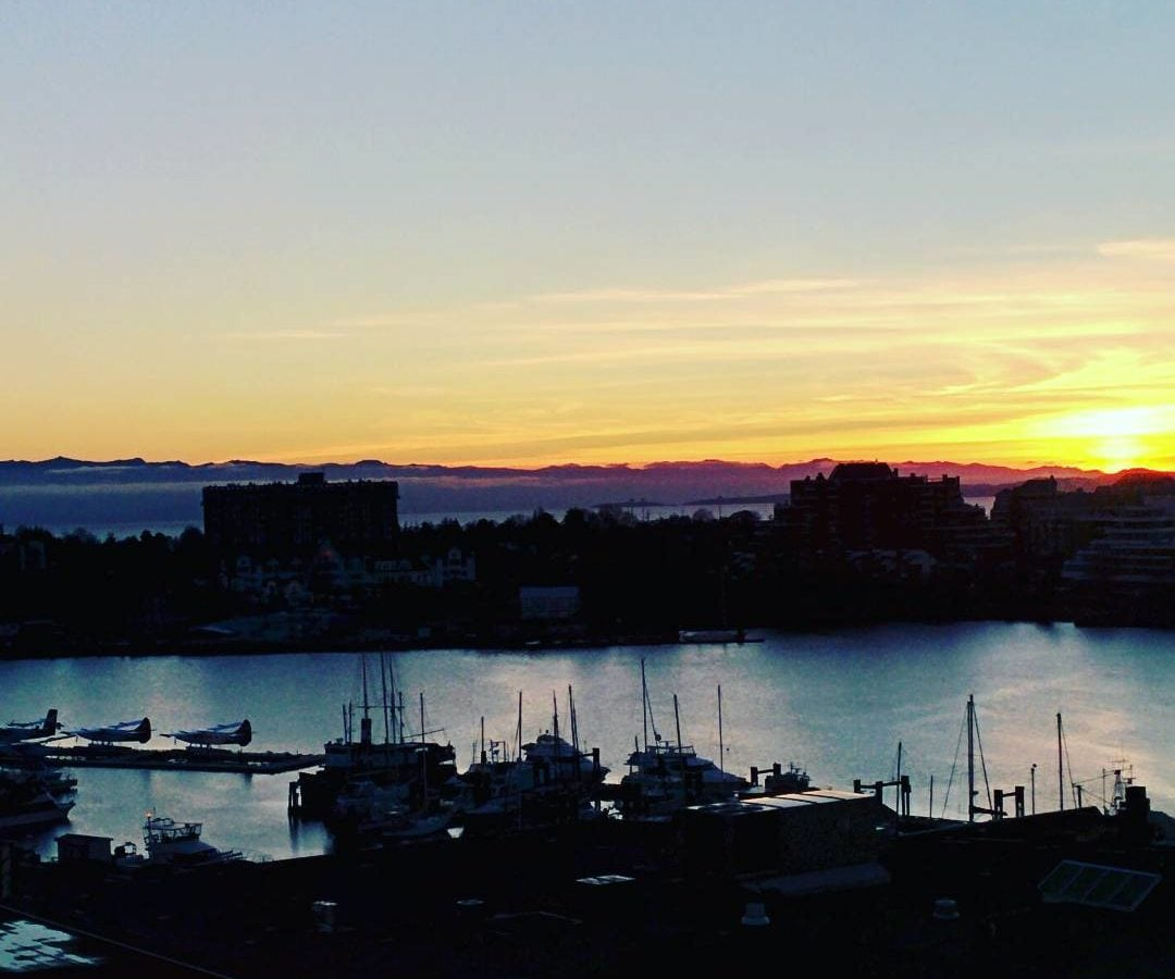 Looking down on the harbour, which is full of sailboats, from a higher vantage point. The boats are silhouettes because the sun is setting in the distance behind them. The same goes for the buildings on the opposite side of the water. The sky is orange on the horizon line, and fades to light blue near the top.