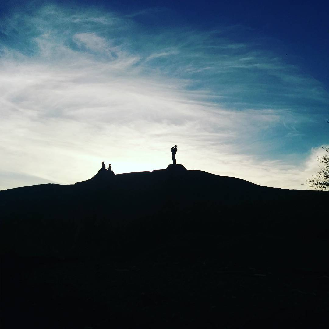 The bottom half of the photo is a rocky space that is black because the sky above and behind it is a bright blue with white clouds, and this brightness is casting the rocky space into shadow. At the top of this rocky hill are the silhouettes of four people. Two are sitting to the left beside each other. There is also an adult sized person in the center with the silhouette of a small person being held on their hip.