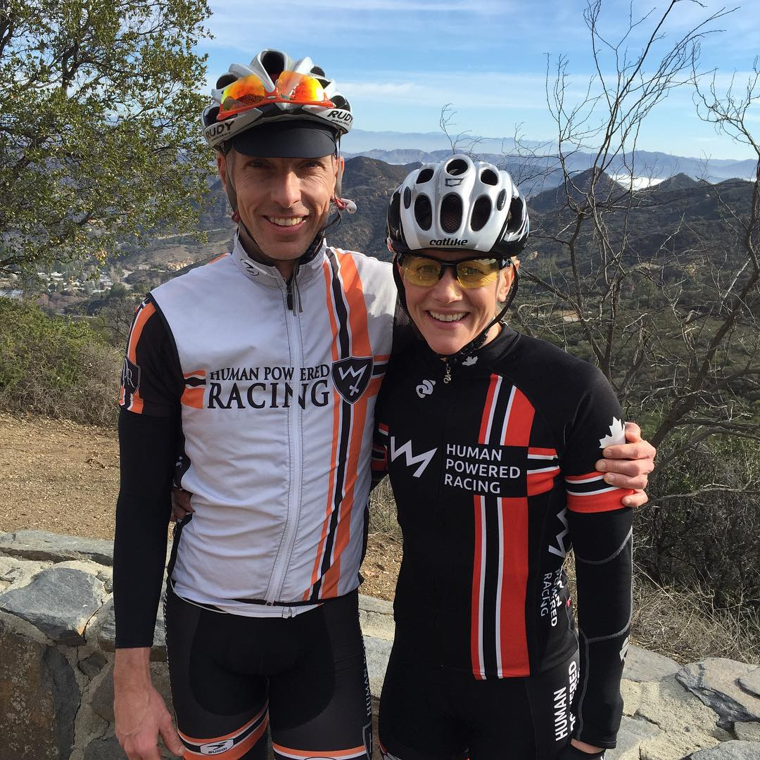 A man (left) and woman (right) have their arms around each other and are smiling. They are wearing biking gear, and the background is a dry landscape with trees and mountains.
