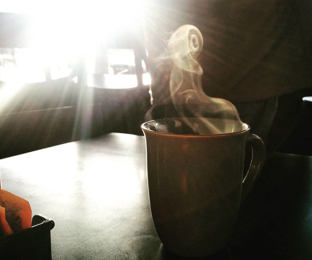 A mug of coffee is slightly right of center, and sitting on a wooden table is steaming, and the steam is in the shape of a tight swirl near the top of the photo. Behind the coffee the sun is glaring through the window and is all we can see in the background.