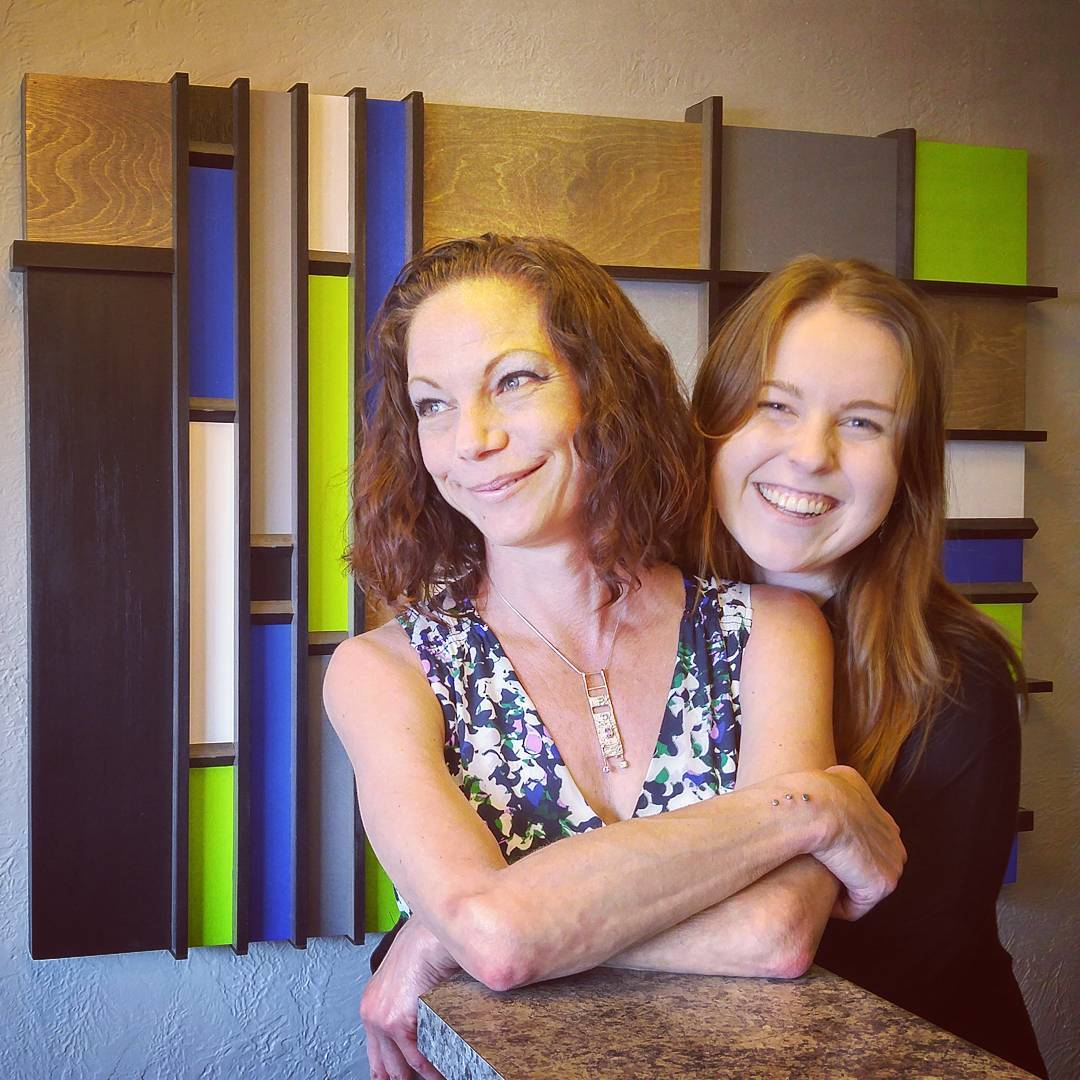 Two women slightly right of center are standing behind a bar like marble reception desk with a green, blue, white, brown, and grey rectangular abstract art piece behind them. The woman in front is looking slightly to the left and her smile looks slightly reluctant. Her arms are crossed on the desk. The woman behind her seems to have her arms around the woman in front, and she is smiling widely. She is slightly further right.