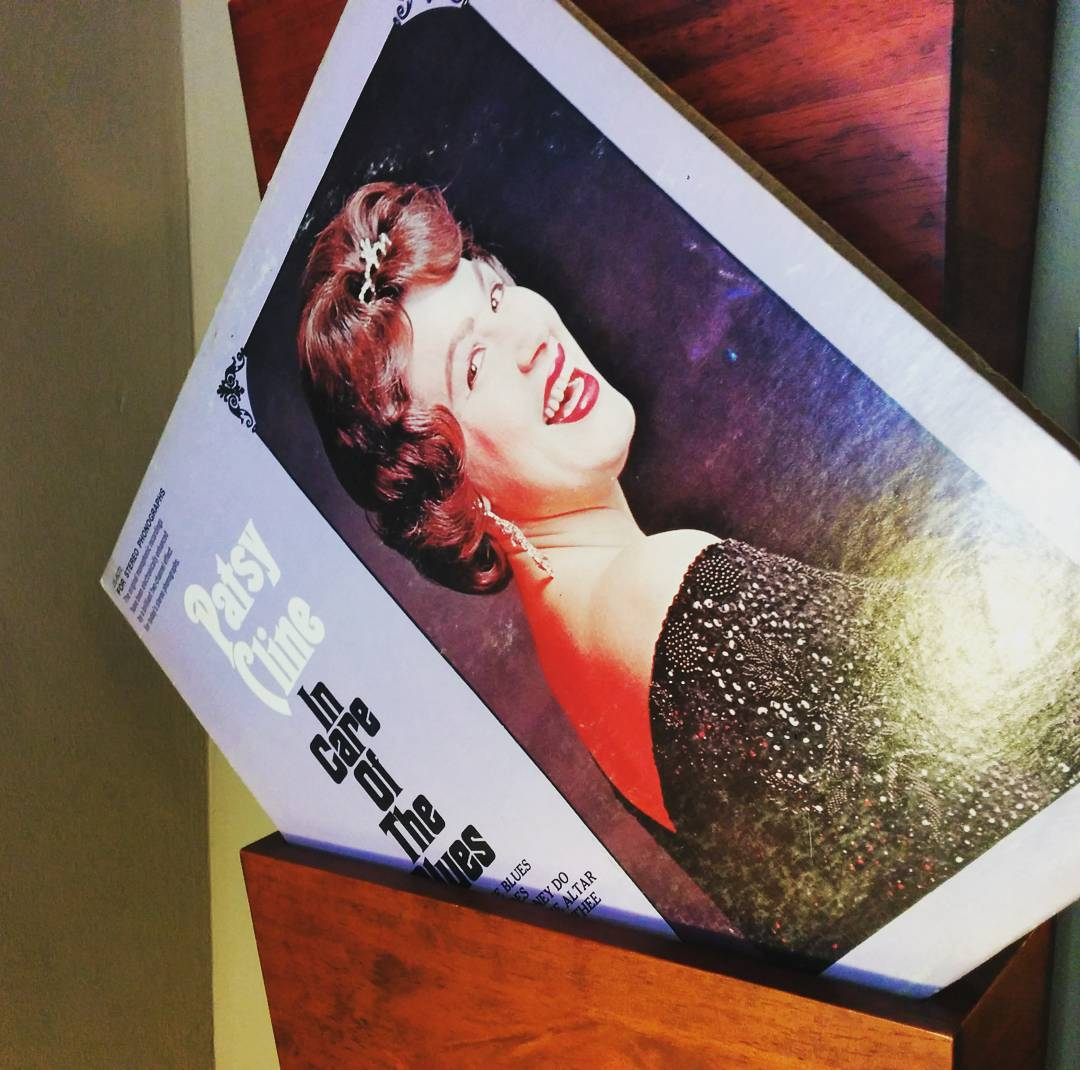 "A purple Patsy Cline record with her photo on the right showing her with short curly brown hair, smiling, and in a black beaded dress. On the left is the name of the record ""In the Care of the Blues."" The record is on an angle standing on its bottom left corner in a wooden case."