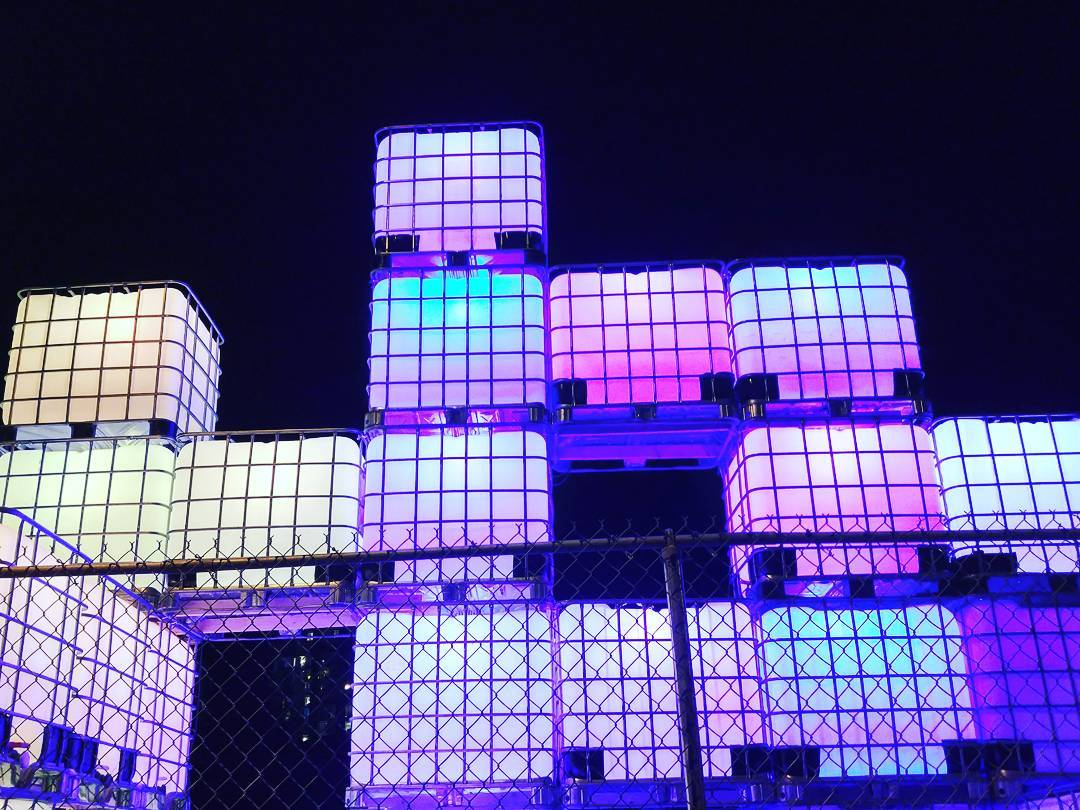 Against a black night sky is an arrangement of lit up cubes stacked on top of one another. They range in colour from yellow, to white, to pink, to blue. There are about 15 in the photo.