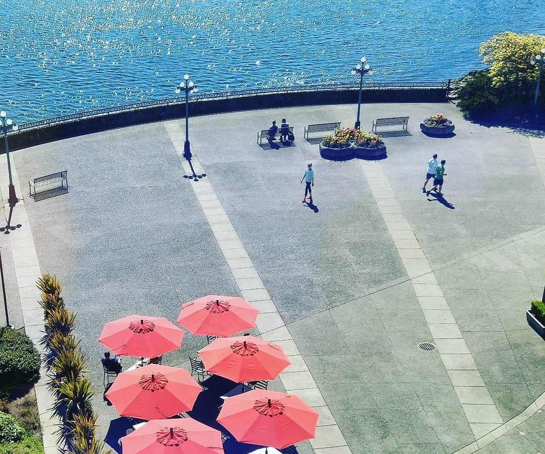 Looking down on a large open paved area with red umbrellas open on the bottom left, three runners in light blue shirts above center on the right, and then blue ocean at the top after the edge of the paved space. It looks bright and sunny, although the sky is not in the photo.