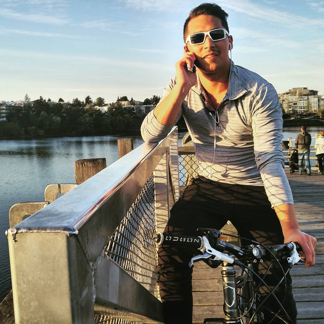 A man on a bike in black pants and a dress shirt is leaning his right elbow on a steel railing and holding a cell phone to his ear with his right hand. The other hand is on the handle bars of the bike. He has sunglasses on. Behind him is a body of water with trees on the other side. The sky is blue with white streaks of cloud.