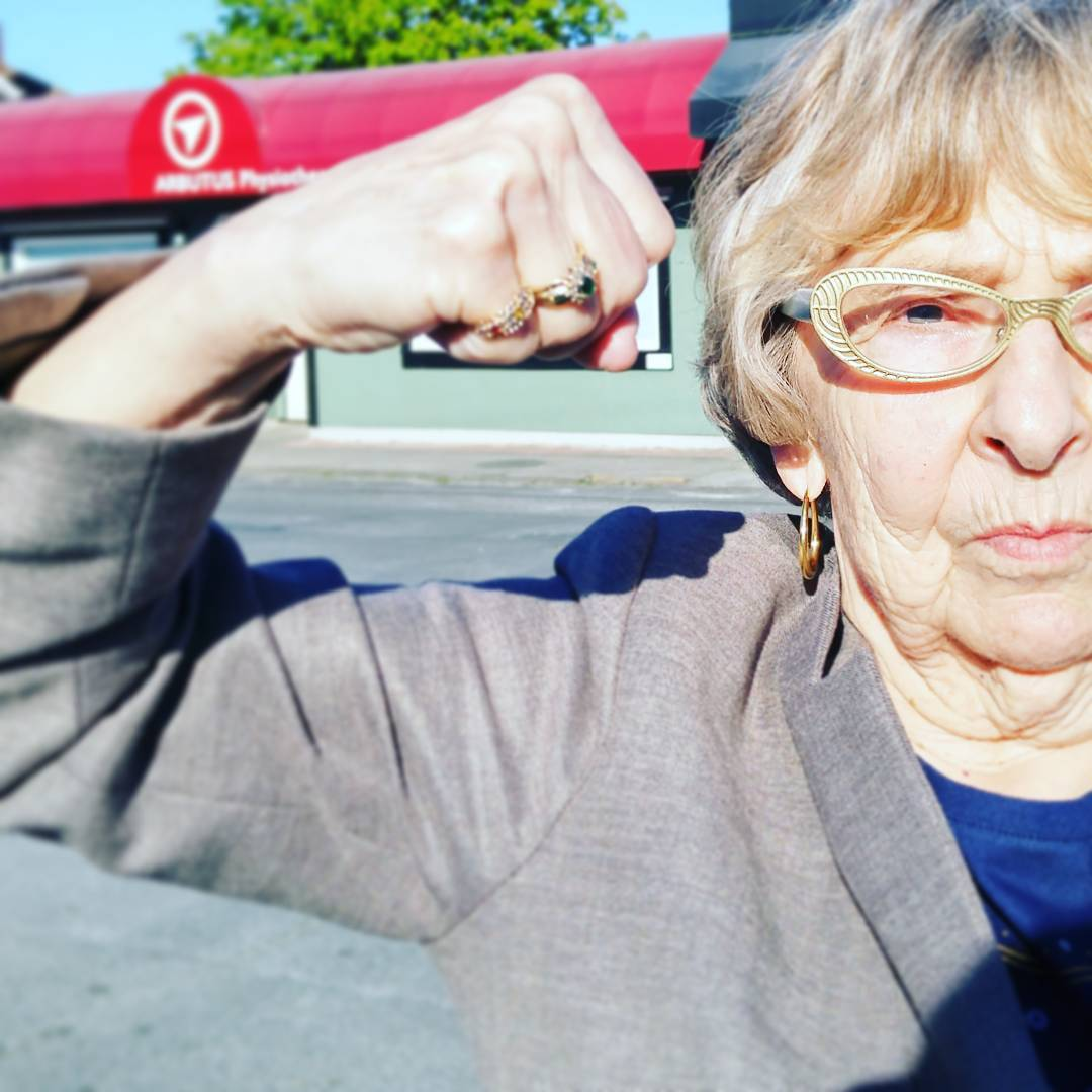 A woman standing to the right is the focus and we can see from the chest up. The right half of her face is visible, and she has cream coloured glasses, short blonde hair, and pursed lips. She looks 60 to 70 years old. She right arm takes up the left half of the photo and is flexed. Out of focus behind her is a red awning with the Arbutus logo of an arrow in a circle printed on it in white. The sky is blue and clear.