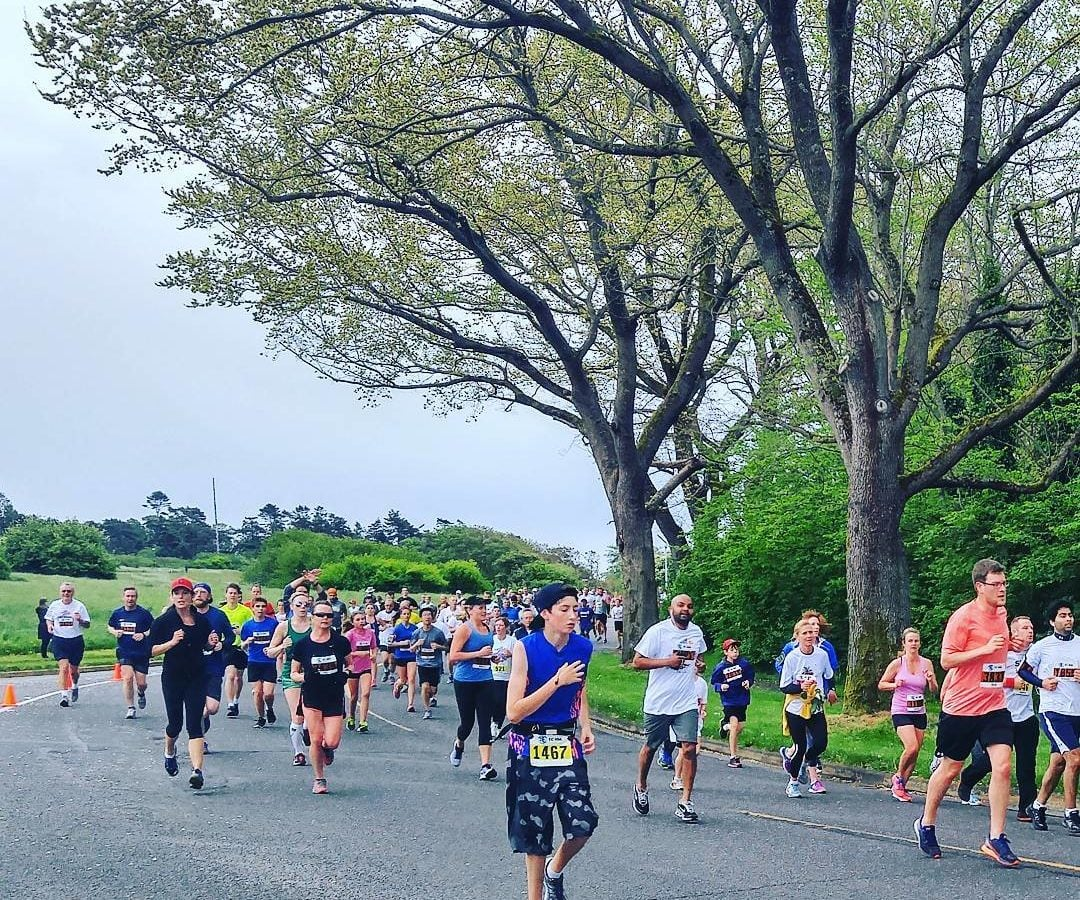 A large group of people running around a bend in the road with race numbers pinned to their stomachs. They are running on the road, and there are green trees and green grass on either side. The sky is a dark, cloudy grey.
