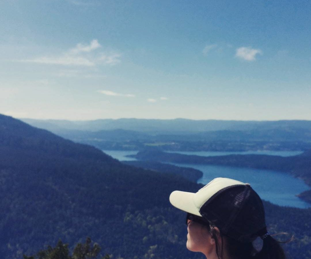 A woman's head and neck are closest to the camera and in the bottom right. She is wearing a black and white baseball cap, has brown hair pulled back into a pony, and is looking out to the left away from the camera. The background is a mountainous landscape covered in evergreen trees, and there are bodies of water visible to the right. The sky is blue with a few white clouds.
