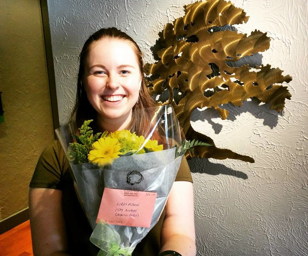 A woman with long brown hair is smiling widely and holding a wrapped bouquet of yellow daisies in front of her. She is indoors in front of a white wall with a bronze cutout of an arbutus tree hanging behind her.