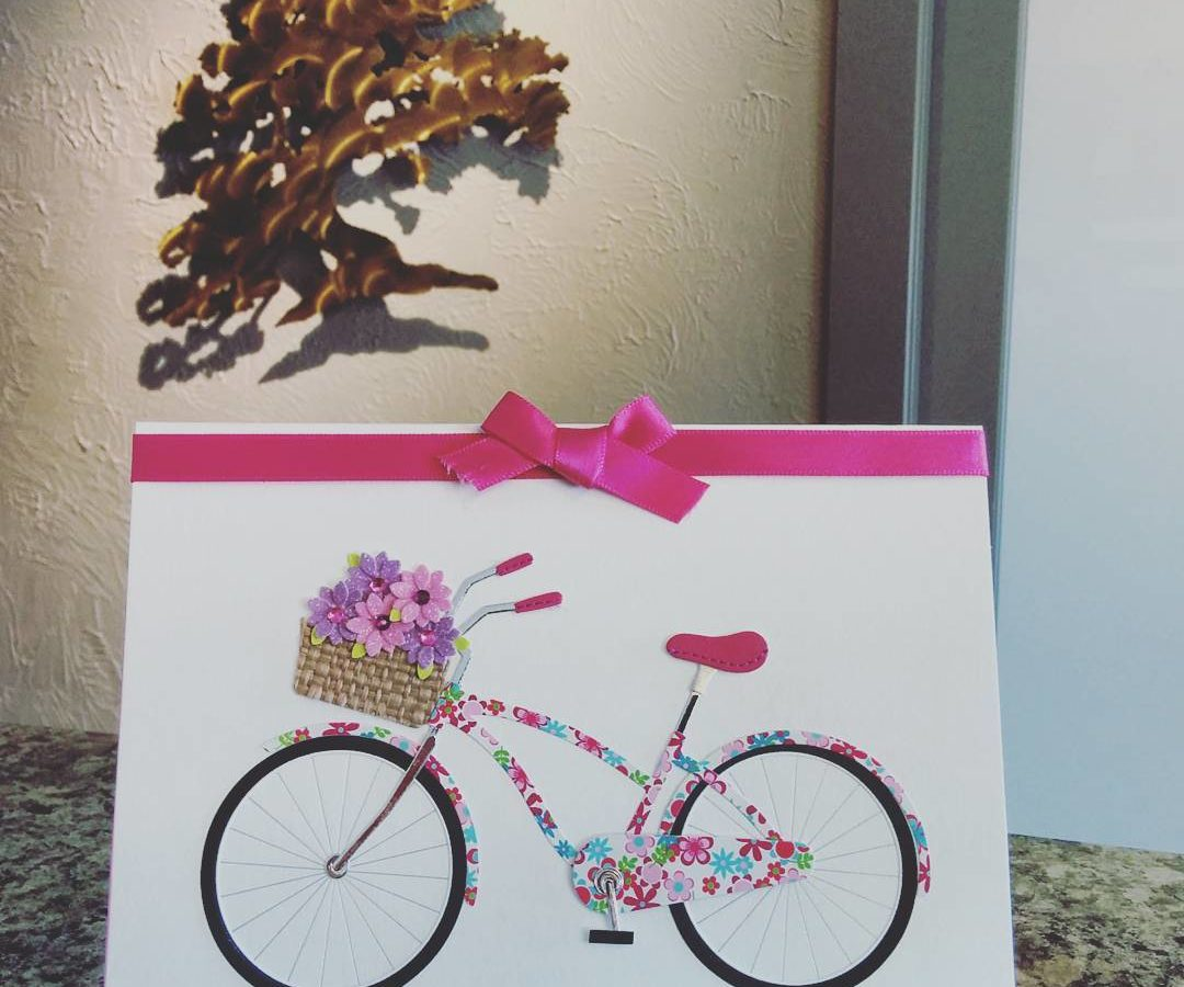 A card is standing on a green marble countertop with a cream coloured wall with a bronze Arbutus Tree cutout hanging on it in the background. The card is white with a pink bike painted on it. The bike also has pink flowers in the handle bar basket. There is also a bright pink ribbon tied in a bow at the top of the card. It is oriented horizontally.