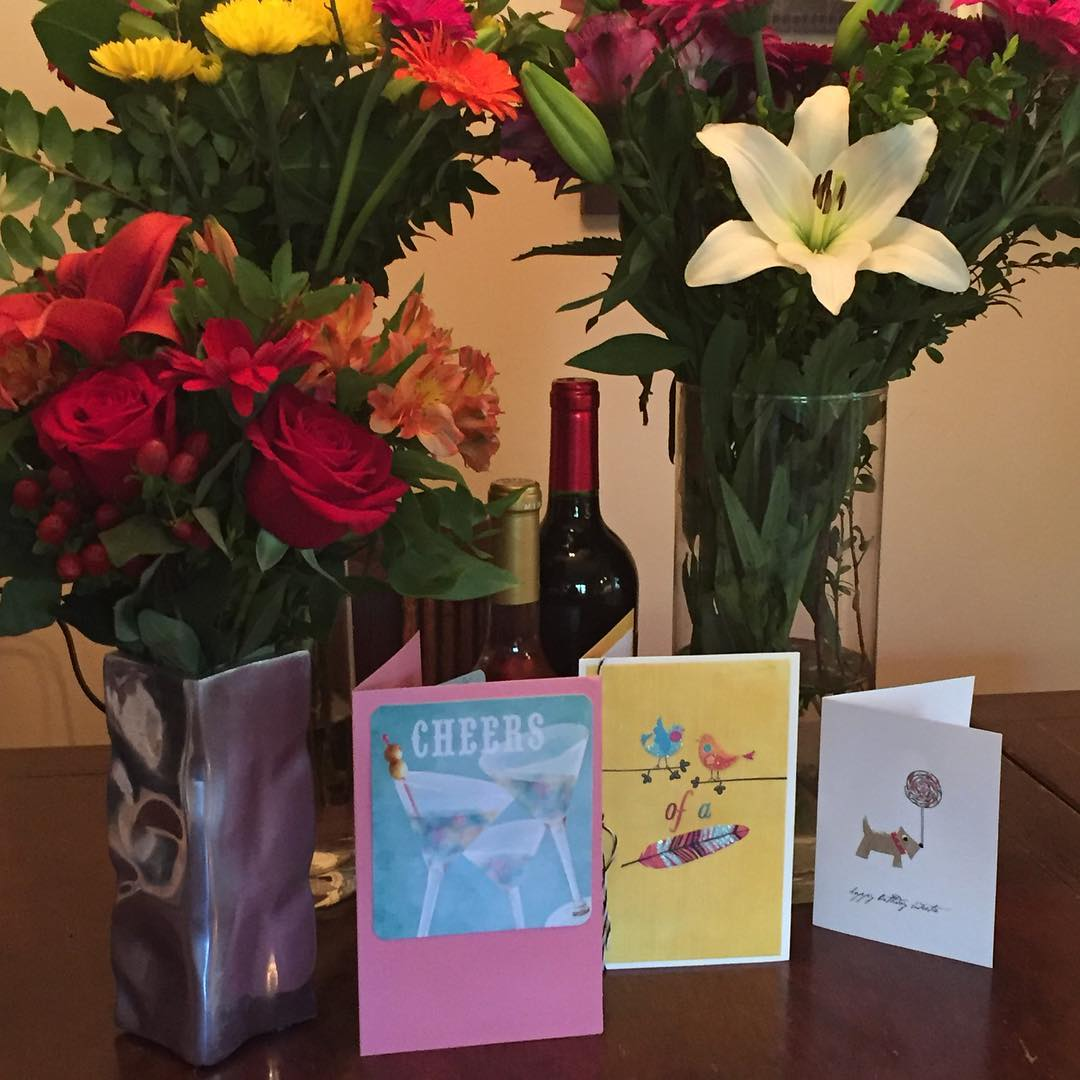 Three class vases of flowers with a bottle of red wine in between them and four cards in front of them are standing against a light brown wall on a dark wooden surface.