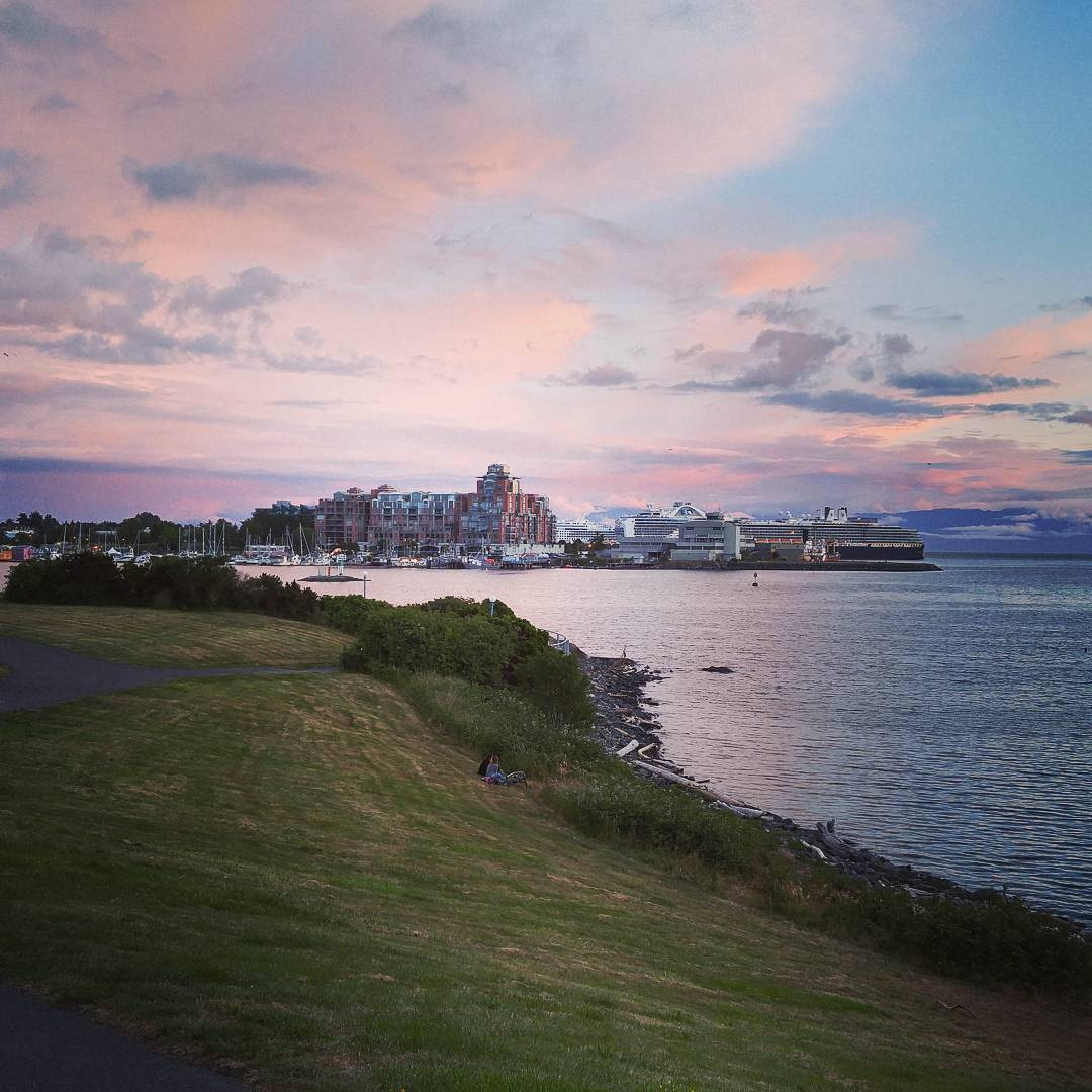 A long stretch of grassy space runs along the left, and the ocean is next to it on the right. In the distance is a cityscape, and the sky is a blue with light pink clouds.