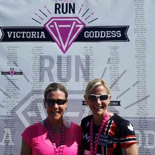 "Two women, one with blonde hair and a black and red ""Human Powered Racing"" shirt and one with brown hair and a bright pink shirt, are standing shoulder to shoulder with their arms around each other. They are wearing sunglasses and smiling. The are in front of a white backdrop that says ""Victoria Goddess Run"" With a pink diamond made of a V and a G in the center."