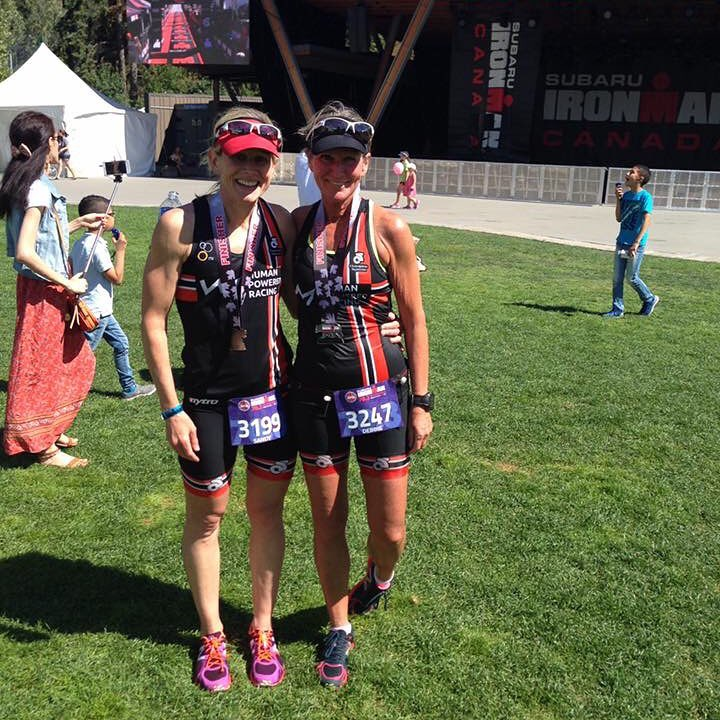 Two women standing on a green field shoulder to shoulder with their arms around each other are smiling. It is a sunny day, and they are wearing matching black, red, and white Human Powered Racing triathlon bodysuits.