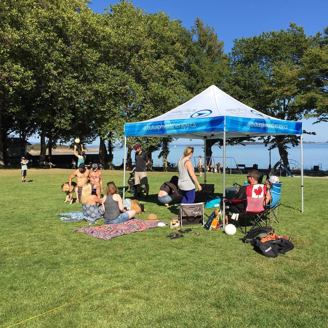 """A group of people sitting on a green grassy field under a white tent with a blue rim on which is printed """"ArbutusPhysiotherapy.ca."""" There are green trees further off around the edges of the field, and straight ahead through the trees the sand and ocean of WIllows Beach are visible. It is a clear blue day."""