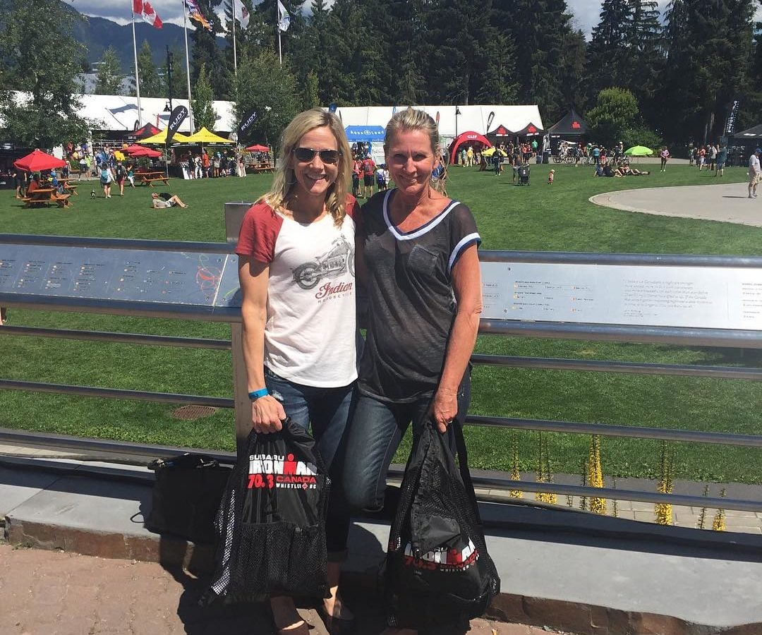"Two women standing shoulder to shoulder with their arms around each other smiling, and both wearing jeans and tshirts. They are standing in front of a green field and there are evergreen trees and a blue cloudy sky in the distance. They are both holding black bags that say ""Ironman 70.3 Canada."""