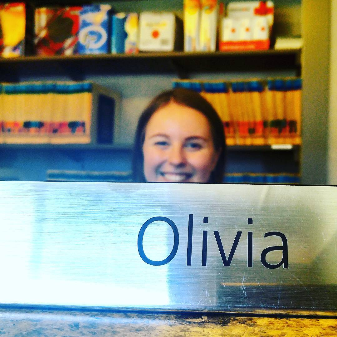"In the foreground is a silver gleaming name plaque sitting on a desk that says ""Olivia."" It is the part in focus. Behind it, and out of focus, is a smiling brown haired woman's head and behind her a bookshelf with yellow files on it."