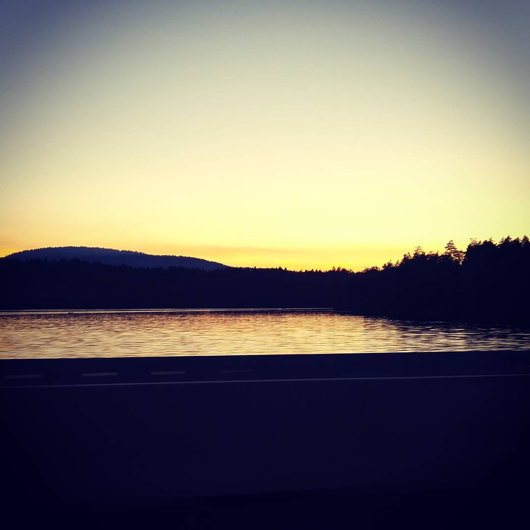 A view across a body of water, which is picking up an orange tinge from the sun. The sun is setting behind the mountains across the water, which makes them into a dark silhouette. The upper edges of the photo are a dark blue.