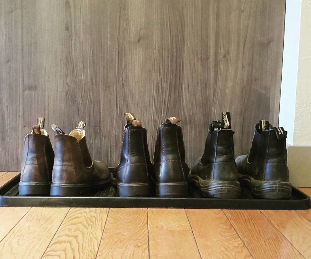 A row of three pairs of brown and black blundstones boots on a black rubber shoe mat on a light hardwood floor. They are in front of a wall that is also wood, though a darker brown.