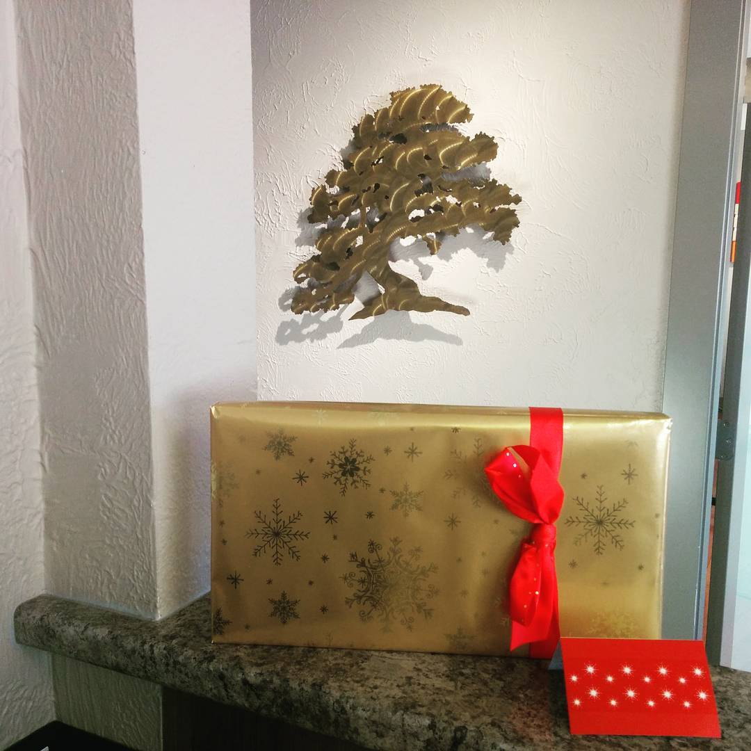 A gold, rectangular gift with a red bow is standing against a cream coloured wall, which also has a bronze cutout of an Arbutus Tree hanging on it. There is a red card standing up in front of and to the right of the gift. Both are on a green marble counter.