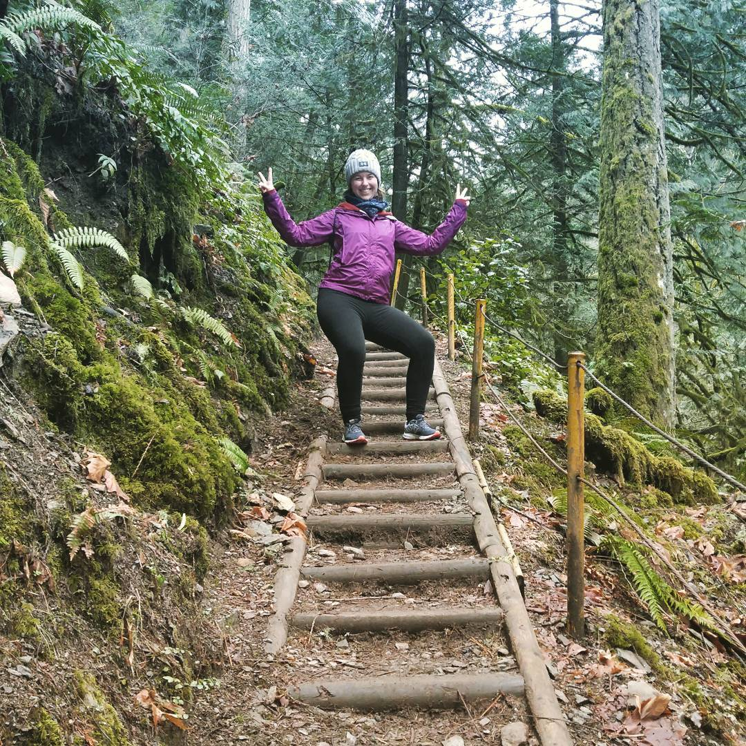 A woman in a purple jacket, a grey beanie hat, and black tights. She is making peace signs with both her hands and smiling. She is standing part way up a stair case in the woods on a path surrounded by evergreen trees.