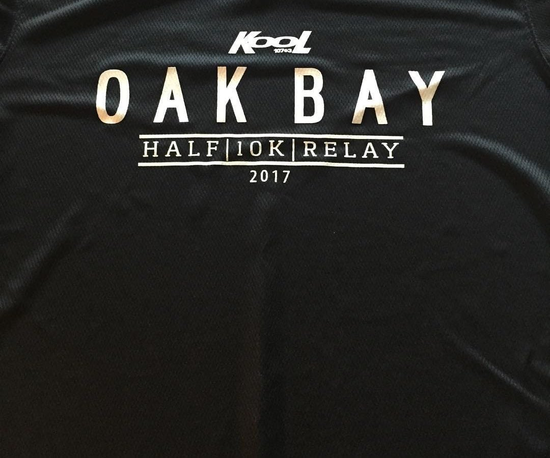 "A close up of the front of a black tshirt with white writing printed on it which reads ""Kool Oak Bay Half/Relay/10k 2017."""