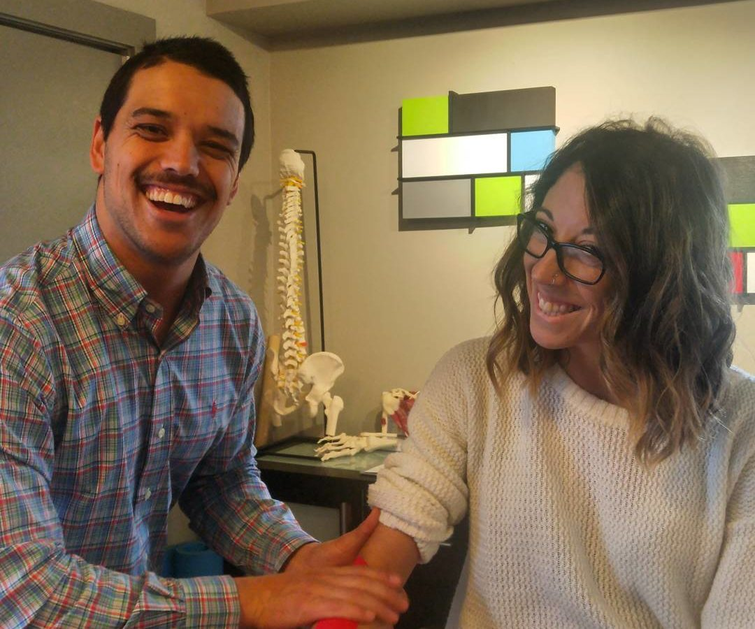 A man and a woman in an office with light brown walls and and anatomical sculptures in the background, most obviously a spine. The man is on the left and he is applying red ktape to the right forearm of the woman who is sitting down on the right. We see them from the waist up. Both are smiling widely at the camera.