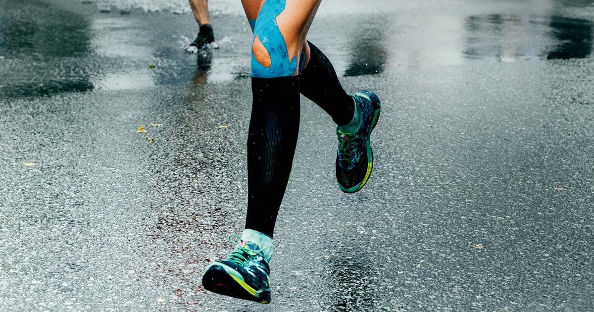 A woman runs in the rain and we can see the blue athletic tape on her knee. Great shoes too.