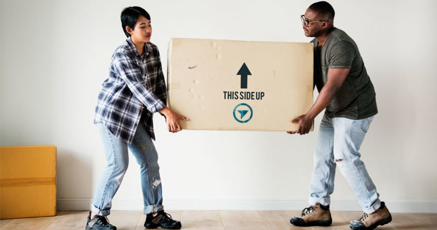 Two people lift a box while moving into their new place.