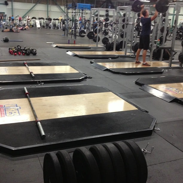 An indoor gym with two rows of light wooden lifting platforms. Each has a metal pole on it and there are round black weights in the foreground. Someone is lighting a bar above his head in the distance, he is out of focus.