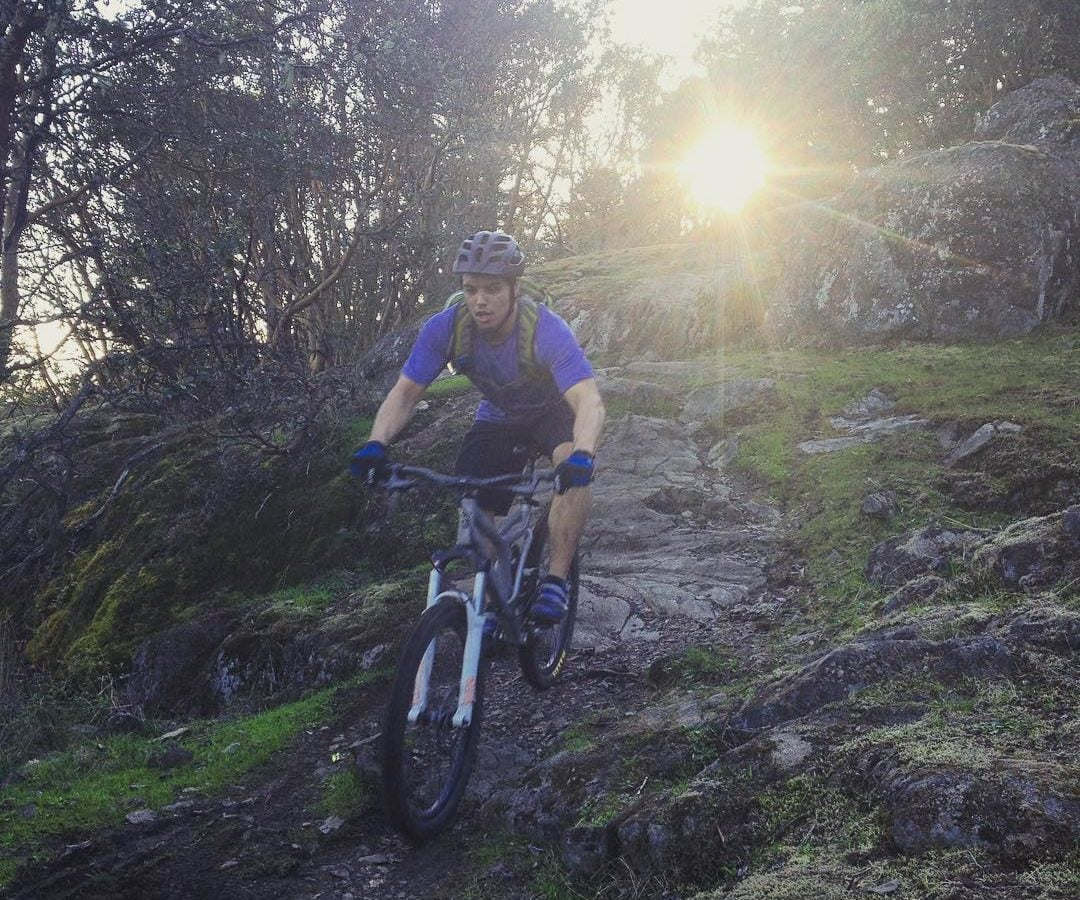 A man in a blue tshirt and a helment biking over damp rocks towards the camera with the sun shining through some thin trees behind him.