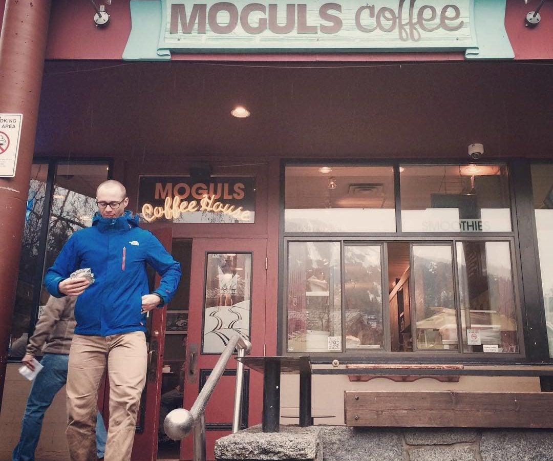 "A man in a blue jacket and brown pants carrying a package in his left hand is coming out of a coffee shop with a sign that says ""Moguls Coffee."""