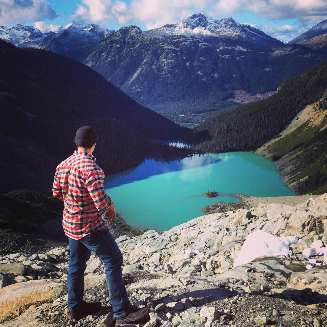 A man facing away from the camera in a red and white plaid shirt and jeans is standing on rocky ground looking out (and down on) a bright blue turquoise lake surrounded by evergreen covered hills to the left and right. On the other side of the lake a large mountain rises up into a blue sky.