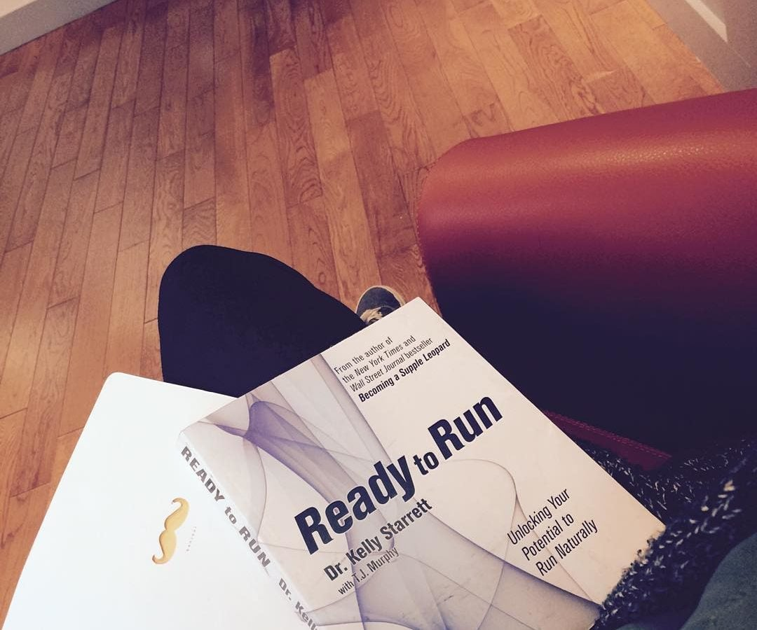 "A book that says ""Ready to Run"" by Dr. Kelly Starrett"" is sitting on someone's thigh with a hardwood floor below."
