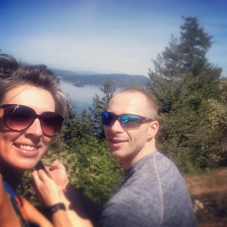 A woman and a man are facing the camera and smiling. Both are wearing sunglasses. There are trees behind them, and the ocean in the distance.