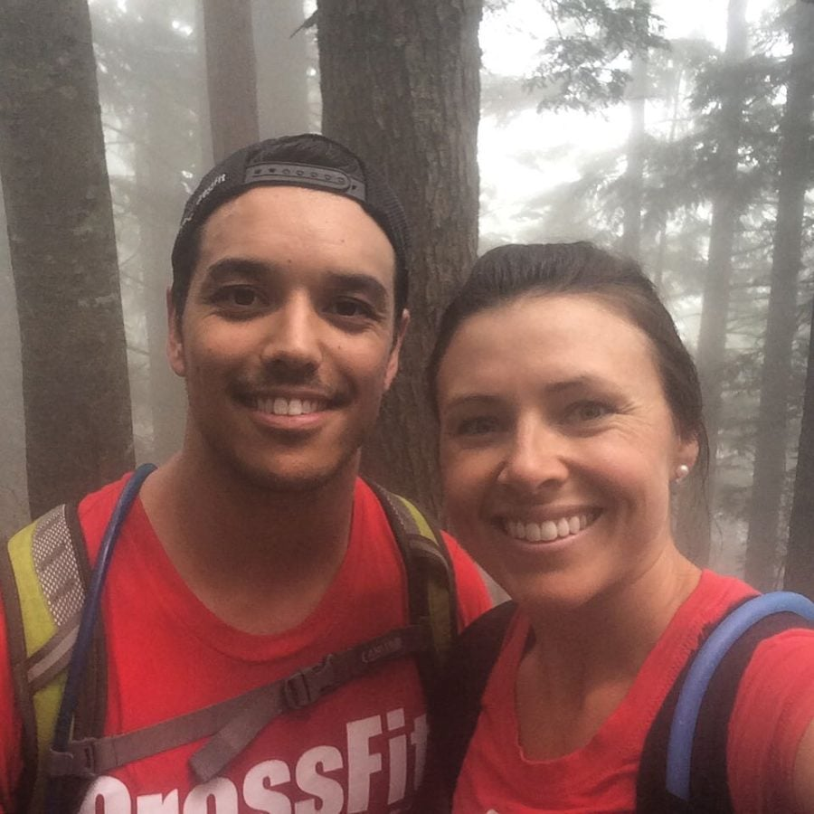 A man on the left and a woman on the right both wearing backpacks and red tshirts. They are shoulder to shoulder and smiling widely and the camera. Tall evergreen trees and fog are behind them.